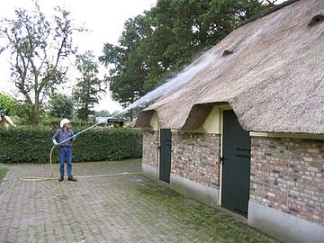 Applying algae repellent on a thatched roof in the Netherlands.