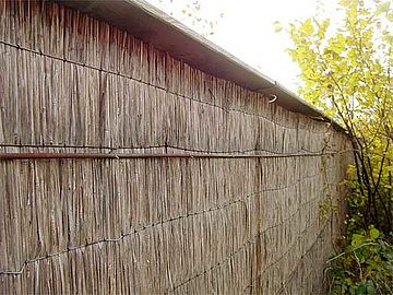 Reed panels on a timber construction with a bevelled wooden board as protection against weathering for the edges of the reed panels.